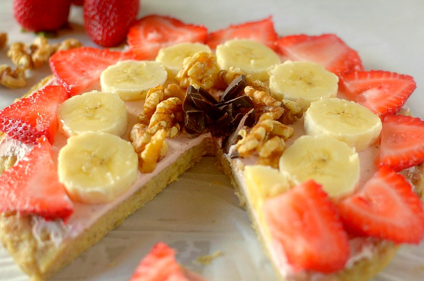 This Healthy Banana Bread Fruit Pizza is a delicious dessert, breakfast or snack! It has a banana bread-like crust and is topped with a strawberry cream cheese frosting, fruit, nuts and chocolate. It is completely gluten-free, paleo and has a vegan option!